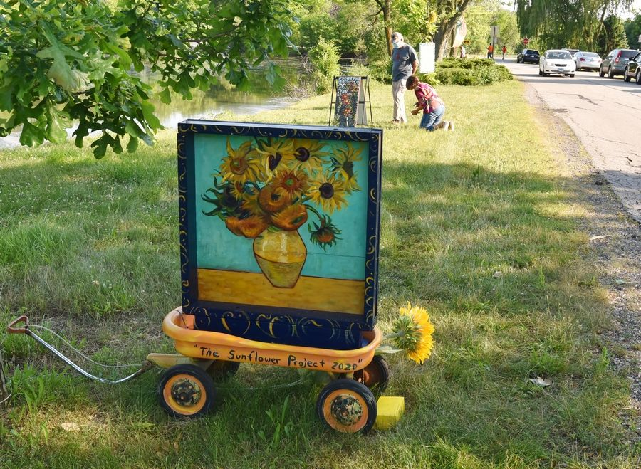 "Artist Kate Tully gave the pop-up art gallery a name when she painted this wagon with ""The Sunflower Project 2020"" on the western shore of Hillcrest Lake in Prospect Heights. Several area artists have continued to add to the project, like June Nichols, who is installing her mosaic piece in the background."
