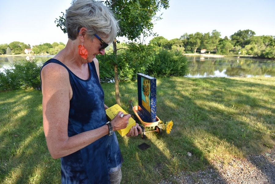 Kate Tully signs a brick to give her artwork a name at Hillcrest Lake in Prospect Heights. She and several other artists have installed sunflower art in a pop-up gallery on the western shore of the lake, but now the city wants them to take it down unless they receive a permit.