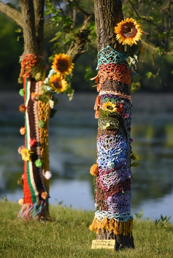 Trees are wrapped in yarn in a piece by artist Olivia Menzia as part of a pop-up gallery on the western shore of Hillcrest Lake in Prospect Heights.