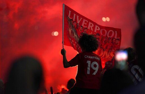 Liverpool supporters celebrate as they gather outside of Anfield Stadium in Liverpool, England, Thursday, June 25, 2020 after Liverpool clinched the English Premier League title. Liverpool took the title after Manchester City failed to beat Chelsea on Wednesday evening.