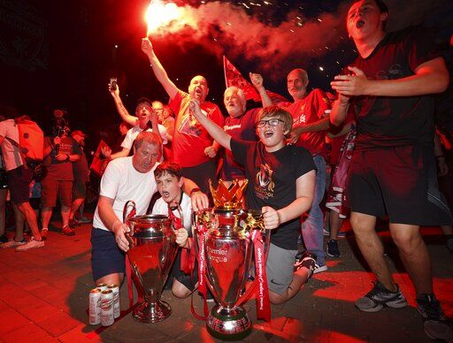 Liverpool supporters with replica Premier League and Champions League trophies as they celebrate outside of Anfield Stadium in Liverpool, England, Thursday, June 25, 2020 after Liverpool clinched the English Premier League title. Liverpool took the title after Manchester City failed to beat Chelsea on Wednesday evening.