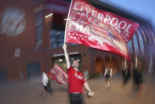 A Liverpool supporter celebrates outside Anfield Stadium in Liverpool, England, Thursday, June 25, 2020 after hearing Chelsea had scored in the English Premier League soccer match between Chelsea and Manchester City. Liverpool will be crowned Premier League champions if Manchester City fail to beat Chelsea.