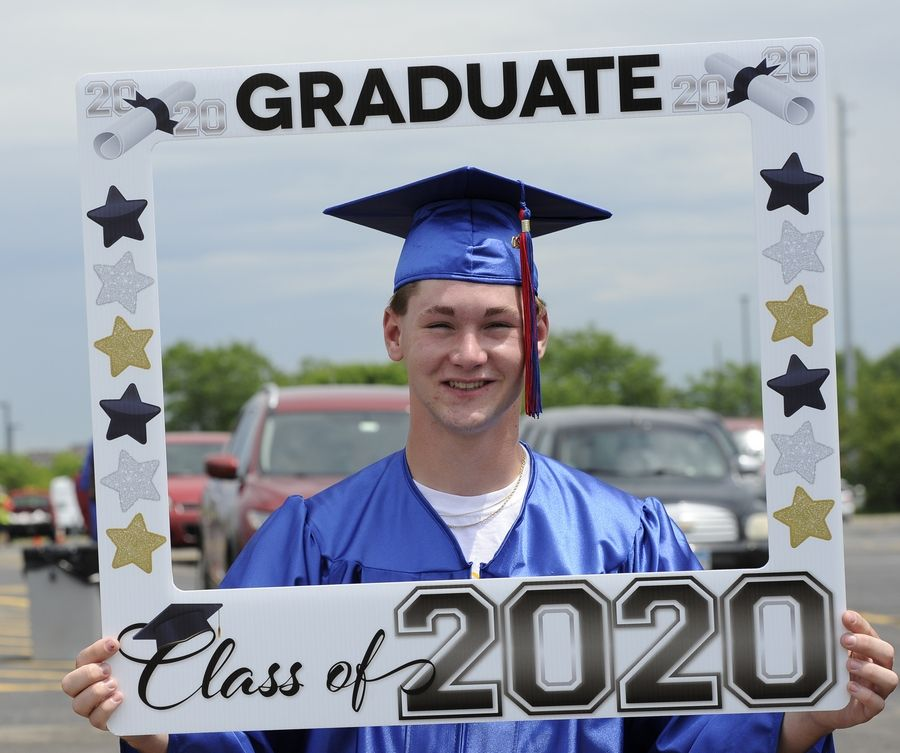 Dundee-Crown grad Peyton Rice, 18, of Algonquin poses with sign that his mom had in the trunk of the car Friday.