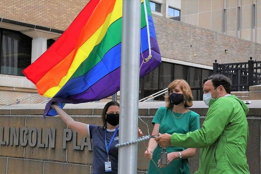 From left, Lake County Board member Julie Simpson, board Chair Sandy Hart and facilities Director Carl Kirar raise a rainbow flag at the county government center in Waukegan on Friday to commemorate the 50th anniversary of the first LGBTQ Pride march.