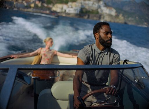 "This image released by Warner Bros. Entertainment shows Elizabeth Debicki, left, and John David Washington in a scene from ""Tenet."" Warner Bros. says it is delaying the release of Christopher Nolan's sci-fi thriller 'œTenet'� until Aug. 12. (Melinda Sue Gordon/Warner Bros. Entertainment via AP)"