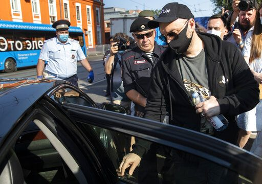 Russian film and theater director Kirill Serebrennikov, right, wearing a face mask to protect against coronavirus, leaves the Meshchansky court after hearings in Moscow, Russia, Friday, June 26, 2020. A Moscow judge convicted an acclaimed Russian theater director of embezzling state funds and imposed a three-year suspended sentence Friday in a case widely seen as politically motivated.