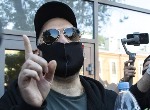 Russian film and theater director Kirill Serebrennikov, wearing a face mask to protect against coronavirus, gestures as he leaves the Meshchansky court after hearings in Moscow, Russia, Friday, June 26, 2020. A Moscow judge convicted an acclaimed Russian theater director of embezzling state funds and imposed a three-year suspended sentence Friday in a case widely seen as politically motivated.