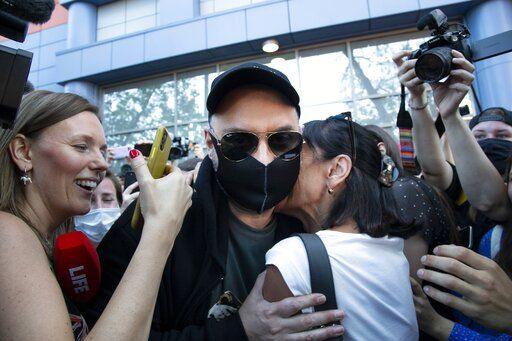 Russian film and theater director Kirill Serebrennikov, wearing a face mask to protect against coronavirus to protect against coronavirus, greets his supporters and colleagues as he leaves the Meshchansky court after hearings in Moscow, Russia, Friday, June 26, 2020. A Moscow judge has convicted an acclaimed Russian theater director of embezzling state funds and imposed a three-year suspended sentence in a case widely seen as politically motivated. Kirill Serebrennikov and his associates were found guilty of fraud and embezzling 129 million rubles (over $1.8 million) of state funding for a theater project.