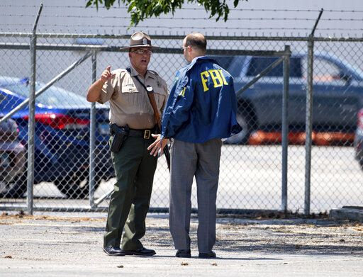 A member of the FBI talks with an Illinois State Police trooper during an active shooter situation at the Bunn-O-Matic warehouse on Stevenson Drive, Friday, June 26, 2020, in Springfield, Ill. Police say officers are searching for a gunman at a warehouse in the Illinois state capital after at least one person was shot and wounded. (Justin L. Fowler/The State Journal-Register via AP)
