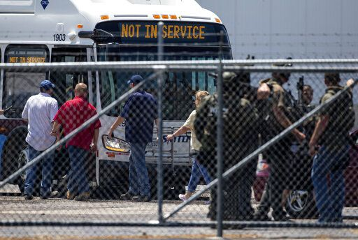 People board an SMTD bus after being cleared from building C1 during an active shooter situation at the Bunn-O-Matic warehouse on Stevenson Drive, Friday, June 26, 2020, in Springfield, Ill. Police say officers are searching for a gunman at a warehouse in the Illinois state capital after at least one person was shot and wounded. (Justin L. Fowler/The State Journal-Register via AP)