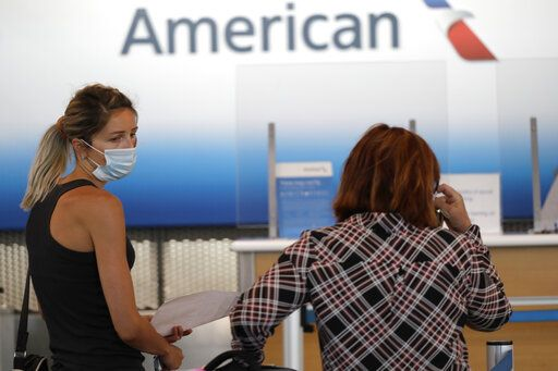 Travelers wear mask as they wait at the American Airlines ticket counter in Terminal 3 at O'Hare International Airport Tuesday, June 16, 2020, in Chicago. Beginning June 16 at American Airlines and June 18 at United Airlines, all passengers and crew members will be required to wear masks to prevent the spread of the coronavirus.