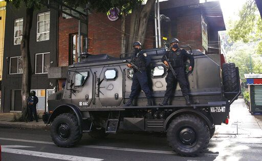 A police vehicle arrives to the place where an abandoned vehicle that is believed to have been used by gunmen in an attack against the chief of police was found, in Mexico City, Friday, June 26, 2020. Heavily armed gunmen attacked and wounded Omar Garcia Harfuch in a brazen operation that left an unspecified number of dead, Mayor Claudia Sheinbaum said Friday.