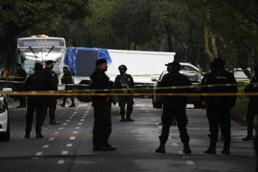 Police stand guard at a crime scene where the chief of police was attacked by gunmen in the early morning hours, in Mexico City, Friday, June 26, 2020.  Heavily armed gunmen attacked and wounded Omar Garcia Harfuch in a brazen operation that left an unspecified number of dead, Mayor Claudia Sheinbaum said Friday.