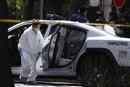 A forensic investigator inspects a police vehicle at the scene where the Mexican capital's police chief was attacked by gunmen in Mexico City, Friday, June 26, 2020. Heavily armed gunmen attacked and wounded Omar García Harfuch in an operation that left several dead.