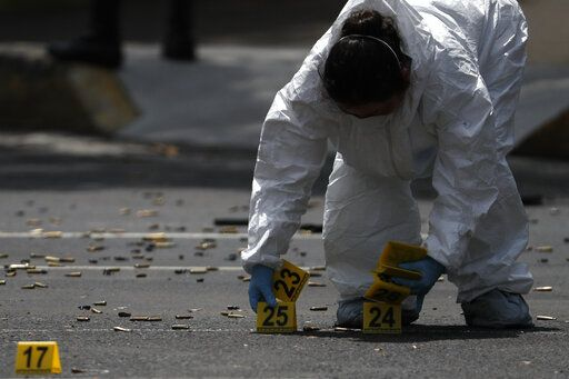 A forensic investigator tags cartridges at the scene where the Mexican capital's police chief was attacked by gunmen in Mexico City, Friday, June 26, 2020. Heavily armed gunmen attacked and wounded Omar GarcÃŒa Harfuch in an operation that left several dead.
