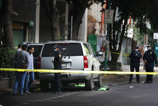 An abandoned vehicle that is believed to have been used by gunmen in an attack against the chief of police is sealed off with yellow tape and guarded by police, in Mexico City, Friday, June 26, 2020. Heavily armed gunmen attacked and wounded Omar Garcia Harfuch in a brazen operation that left an unspecified number of dead, Mayor Claudia Sheinbaum said Friday.