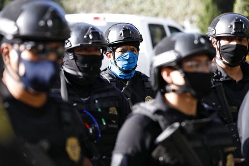 Police arrive to the scene where security secretary, Omar García Harfuch, was attacked by gunmen in the early morning hours in Mexico City, Friday, June 26, 2020. Heavily armed gunmen attacked and wounded Mexico City's police chief in a brazen operation that left an unspecified number of dead, Mayor Claudia Sheinbaum said Friday.