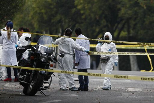 Forensic investigators and police work the scene where security secretary, Omar García Harfuch, was attacked by gunmen in the early morning hours in Mexico City, Friday, June 26, 2020. Heavily armed gunmen attacked and wounded Mexico City's police chief in a brazen operation that left an unspecified number of dead, Mayor Claudia Sheinbaum said Friday.