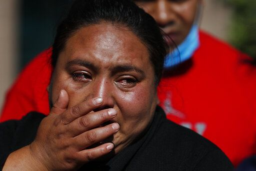 Gabriela Gomez cries after her sister Rosa Gomez was killed at the scene where police chief Omar García Harfuch was attacked by gunmen in Mexico City, Friday, June 26, 2020. Heavily armed gunmen attacked and wounded Mexico City's police chief in an operation that left several people dead.
