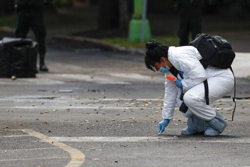 A forensic investigator collects cartridges at the scene where the Mexican capital's police chief was attacked by gunmen in Mexico City, Friday, June 26, 2020. Heavily armed gunmen attacked and wounded Omar García Harfuch in an operation that left several dead.