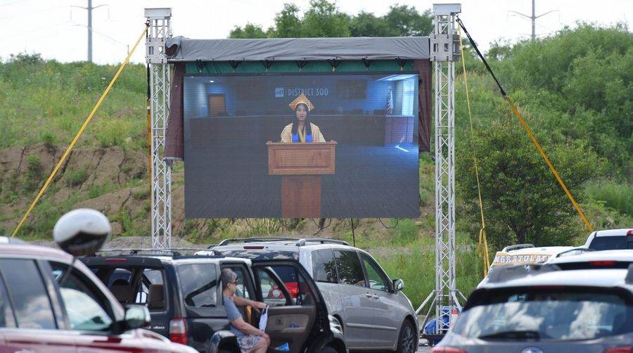 Valedictorian Melissa Tan addresses her classmates in a prerecorded speech at the graduation ceremony for Jacobs High School in the parking lot of the Sears Centre in Hoffman Estates Saturday.