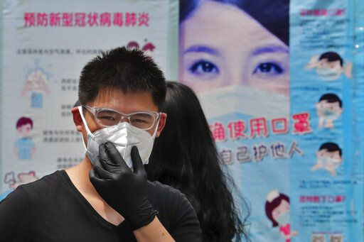 A man wearing groves adjusts his protective face mask as he walks by posters showing a proper way to wear a face mask to help curb the spread of the coronavirus in Beijing, Sunday, June 28, 2020. China has extended COVID-19 tests to newly reopened salons amid a drop in cases while South Korea continues to face new infections as it eases social distancing rules.