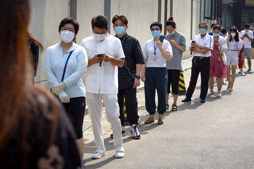 People wearing face masks stand in line for coronavirus tests at a community health clinic in Beijing, Sunday, June 28, 2020. China reported more than a dozen of new confirmed cases of COVID-19 on Sunday, all but a few of them from domestic transmission in Beijing, which has seen a recent spike in coronavirus infections. But authorities in the Chinese capital say a campaign to conduct tests on employees at hair and beauty salons across the city has found no positive cases so far, in a further sign that the recent outbreak has been largely brought under control.