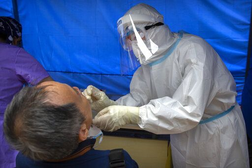 A worker wearing a protective suit swabs a man's throat for a coronavirus test at a community health clinic in Beijing, Sunday, June 28, 2020. China reported more than a dozen of new confirmed cases of COVID-19 on Sunday, all but a few of them from domestic transmission in Beijing, which has seen a recent spike in coronavirus infections. But authorities in the Chinese capital say a campaign to conduct tests on employees at hair and beauty salons across the city has found no positive cases so far, in a further sign that the recent outbreak has been largely brought under control.
