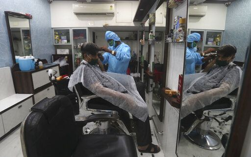A man get a haircut at a salon in Mumbai, India, Sunday, June 28, 2020. India is the fourth hardest-hit country by the COVID-19 pandemic in the world after the U.S., Russia and Brazil.
