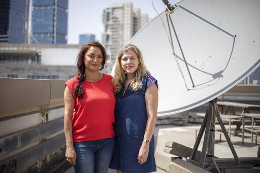 "In this Sunday, June 21, 2020 photo actress Esti Yerushalmi, left, a cast member in ""Tehran"" and Dana Eden, one of the show's creators, pose in Tel Aviv, Israel. Israel's latest hit TV series takes its viewers straight into the heart of the country's archenemy Iran. ""Tehran'� tells the story of a young Mossad operative tasked with hacking into and disabling the Iranian nuclear reactor so the Israeli military can carry out an airstrike.  It's a story arc that touches on many of the region's most pressing fault lines. It's also the latest episode in the golden age of Israeli television, with Apple TV+ purchasing the rights to the eight-part series."