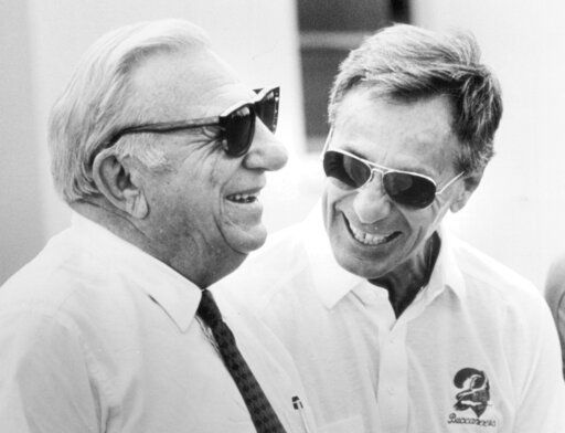 In this 1984 photo, Tampa Bay Buccaneers owner Hugh Culverhouse, left, and general manager Phil Krueger laugh during NFL football practice in Tampa. Fla. Krueger, who helped build a dominant defense as an assistant for 1967 national champion Southern California and later became part of the first coaching staff in Buccaneers' history, died Monday, June 22, 2020, at his home in Pembroke Pines, Fla. He was 90. Krueger coached offense, defense and special teams during more than three decades in the NFL and college. (Fraser Hale/Tampa Bay Times via AP)