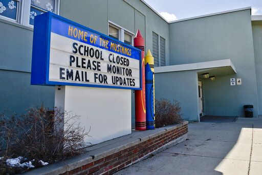 FILE - This Thursday, April 16, 2020 file photo shows a sign announcing an elementary school in Helena, Mont., is closed. When the coronavirus pandemic took hold across the United States in mid-March, forcing schools to close and many children to be locked down in households buffeted by job losses and other forms of stress, many child-welfare experts warned of a likely surge of child abuse. Fifteen weeks later, the worries persist - yet some experts on the front lines, including pediatricians who helped sound the alarm, say they've seen no evidence yet that a marked increase has taken place. (Thom Bridge/Independent Record via AP)