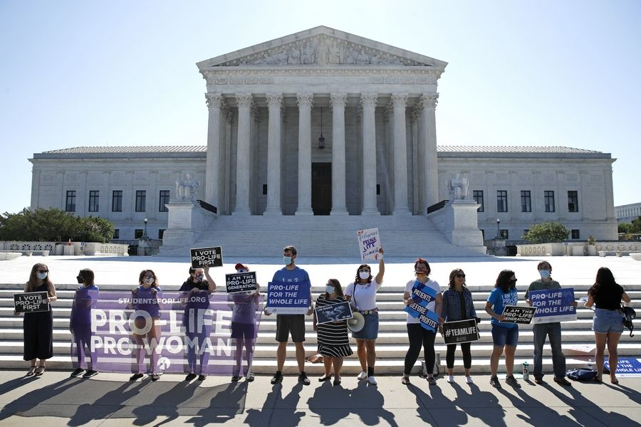 Anti-abortion protesters wait Monday outside the Supreme Court for a decision in Washington on the Louisiana case, Russo v. June Medical Services LLC.