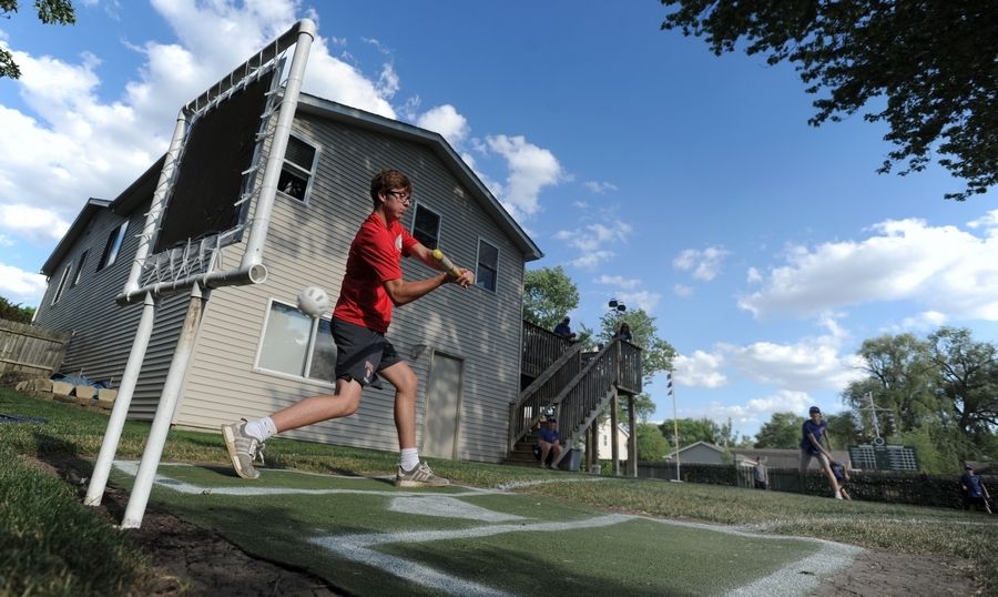 The Wrigley Field Wiffle ball stadium 16-year-old D.J. Dick built in the backyard of his family's Palatine house includes a foul ball screen to keep balls out of a neighbor's yard. Here, Paul Bloomquist, 16, takes a cut during a game.