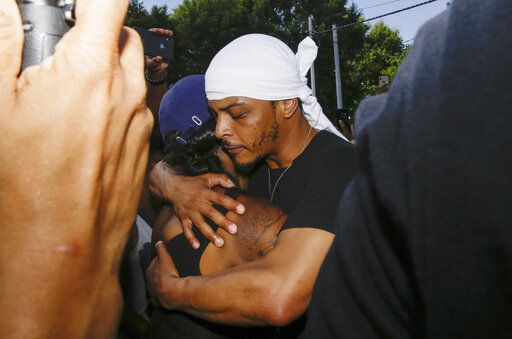 Rapper T.I. hugs a family member of Rayshard Brooks during protests, Saturday, June 13, 2020, near the Wendy's restaurant where Brooks was shot and killed by police Friday evening following a struggle in the restaurant's drive-thru line in Atlanta.