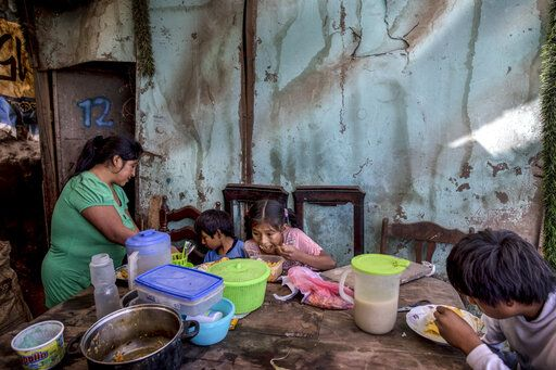 "Consuelo Pascacio's three children; Estiben 4, Estefany, 11, and Javier, 14, dig into a chicken rice stew she picked up at a ""community pot,"" in their home in the Nueva Esperanza neighborhood of Lima, Peru, Monday, June 8, 2020. For many residents the ""community pot"" is their only defense against a hunger that's become a constant feature of life amid the new coronavirus pandemic."