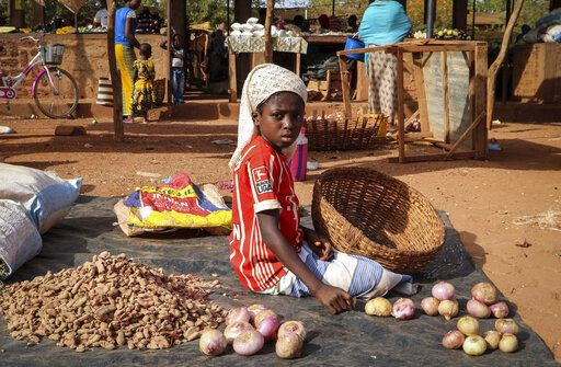 In this Wednesday, May 13, 2020, photo, a child sits on the ground selling onions at a market stall in Tougan, Burkina Faso. Violence linked to Islamic extremists has spread to Burkina Faso's breadbasket region, pushing thousands of people toward hunger and threatening to cut off food aid for millions more.