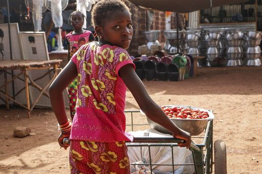 In this Wednesday, May 13, 2020, photo, a girl pushes a cart of food at a market in Tougan, Burkina Faso. Violence linked to Islamic extremists has spread to Burkina Faso's breadbasket region, pushing thousands of people toward hunger and threatening to cut off food aid for millions more.