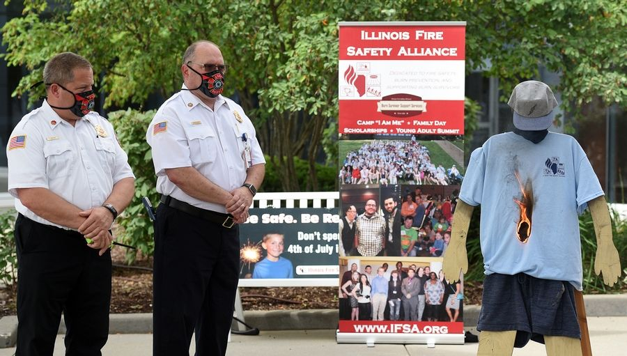 Hoffman Estates Fire Department Deputy Chief Thomas Mackie, from left, and Chief Patrick Fortunato watch as a T-shirt is quickly consumed by flames during a fireworks safety demonstration Tuesday at Amita Health St. Alexius Medical Center in Hoffman Estates.