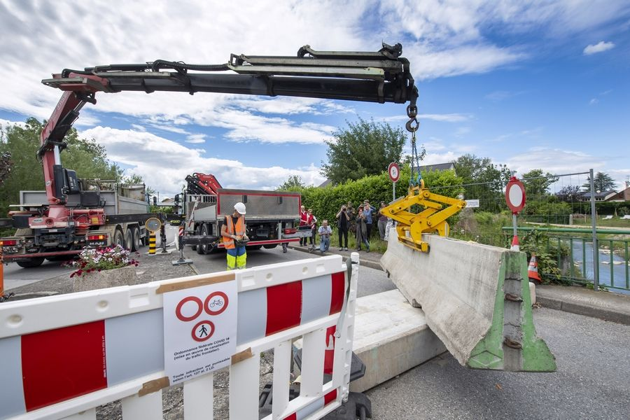 A crane removes the concrete blocks that closed customs access, in Thonex near Geneva, Switzerland. The European Union is set to make public Tuesday a list of countries whose citizens will be allowed to enter 31 European countries, but most Americans are likely to be refused entry for at least another two weeks due to soaring coronavirus infections in the U.S.