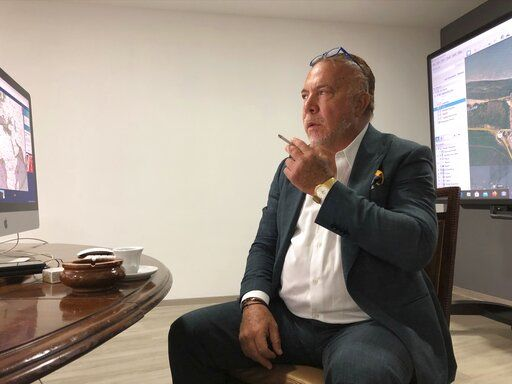 In this April 29, 2020 photo, Venezuelan shipping magnate Wilmer Ruperti smokes a cigarette during an interview in Caracas, Venezuela. As a result of U.S. sanctions on Venezuela, a high-stakes legal fight in U.S. federal court is pitting Ruperti against Greek shipping magnate Evangelos Marinakis, in connection with oil tanker Alkimos carrying high octane gasoline estimated to be worth millions.