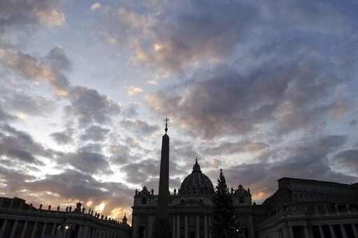 FILE - In this Thursday, Dec. 5, 2019 file photo, the sun sets over St. Peter's Basilica, at the Vatican. Vatican prosecutors have ordered the seizure of documents and computers from the administrative offices of St. Peter's Basilica in an apparently new investigation into financial irregularities in the Holy See. The Vatican said Tuesday that Pope Francis has also named a special commissioner to run the basilica, reorganize its offices, update its statutes to comply with new Vatican norms on procurement contracts and to 'œclarify its administration.'�