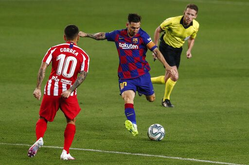 Barcelona's Lionel Messi, center, kicks the ball in front Atletico Madrid's Angel Correa during the Spanish La Liga soccer match between FC Barcelona and Atletico Madrid at the Camp Nou stadium in Barcelona, Spain, Tuesday, June 30, 2020.