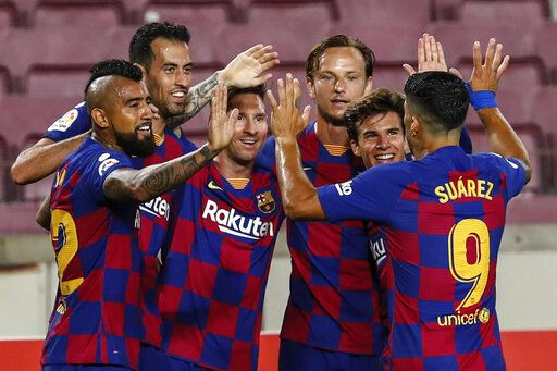FC Barcelona players celebrate their opening goal during the Spanish La Liga soccer match between FC Barcelona and Atletico Madrid at the Camp Nou stadium in Barcelona, Spain, Tuesday, June 30, 2020.