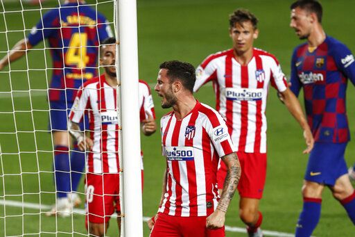 Atletico Madrid's Saul, center, celebrates after scoring his side's second goal during the Spanish La Liga soccer match between FC Barcelona and Atletico Madrid at the Camp Nou stadium in Barcelona, Spain, Tuesday, June 30, 2020.