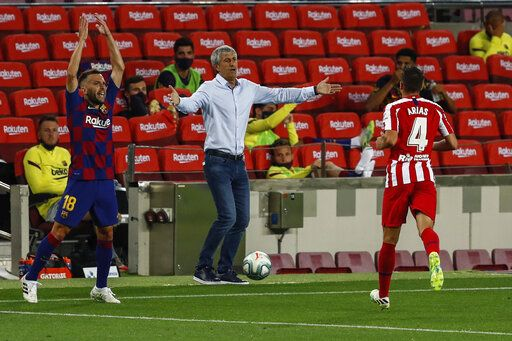 Barcelona's head coach Quique Setien, center, gestures during the Spanish La Liga soccer match between FC Barcelona and Atletico Madrid at the Camp Nou stadium in Barcelona, Spain, Tuesday, June 30, 2020.