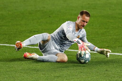 Barcelona's goalkeeper Marc-Andre ter Stegen stops the ball during the Spanish La Liga soccer match between FC Barcelona and Atletico Madrid at the Camp Nou stadium in Barcelona, Spain, Tuesday, June 30, 2020.