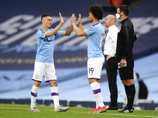 Manchester City's Phil Foden, left, gestures with teammate Leroy Sane as he is substituted during the English Premier League soccer match between Manchester City and Burnley at Etihad Stadium, in Manchester, England, Monday, June 22, 2020.
