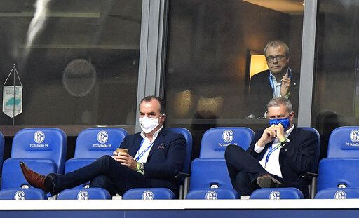 FILE-In this May 24, 2020 file photo Schalke boss Clemens Toennies, left, watches from the tribune with financial director Peter Peters, up, and supervisory board Jens Buchta, right, during the German Bundesliga soccer match between FC Schalke 04 and FC Augsburg at the Veltins-Arena in Gelsenkirchen, Germany. Longtime Schalke chairman Clemens Toennies has stepped down following fan unrest over the German soccer club's lengthy winless run and an outbreak of coronavirus at a slaughterhouse owned by his company.