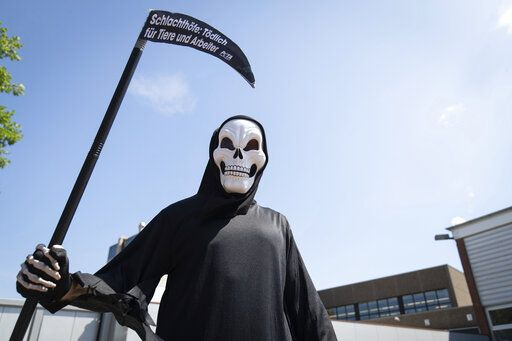 "An activist of the animal protection organization Peta disguised as death stands in front of a delivery entrance of the meat and sausage manufacturer Schulte in Dissen, Germany, Thursday, June 25, 2020. Schulte belongs to the Tönnies Group. Under the motto ""Slaughterhouses: Deadly for humans and animals"", Peta wants to draw attention to the conditions in meat factories after the outbreak of the coronavirus at meat producers. (Friso Gentsch/dpa via AP)"